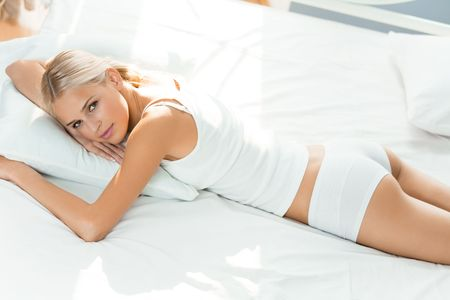 lazyness: Young happy woman waking up at bedroom Stock Photo