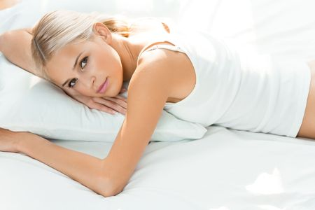 Young happy woman waking up at bedroom photo