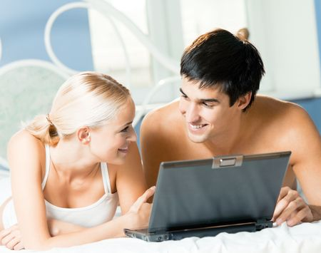 Young happy couple with laptop at bedroom Stock Photo - 7541823