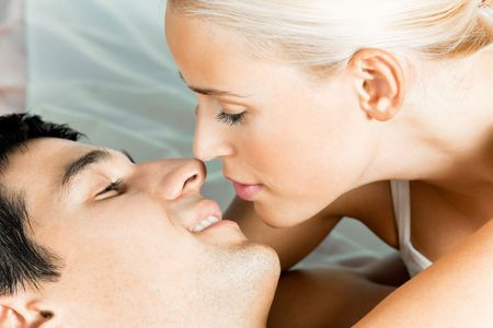 Young attractive happy amorous kissing couple at bedroom photo