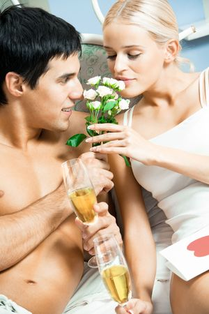 Young happy couple celebrating with champagne at bedroom photo