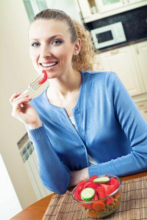 Young happy smiling woman eating vegetarian salad photo