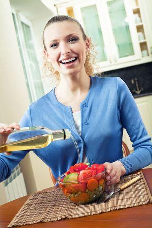 Young happy woman making salad at home photo