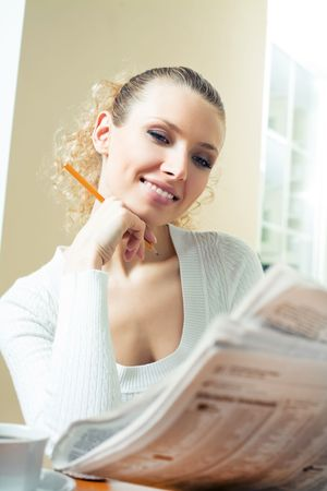 Young happy woman with newspaper at home photo