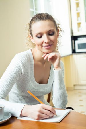 Young woman with notebook or organiser at home Stock Photo - 7582075