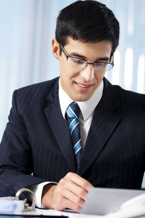 Successful businessman with documents at office Stock Photo - 7582142