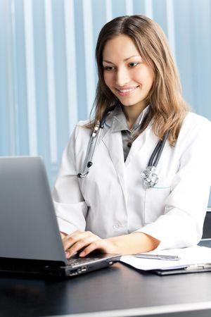 nursing treatment: Feliz m�dico o enfermera con ordenador port�til en la Oficina