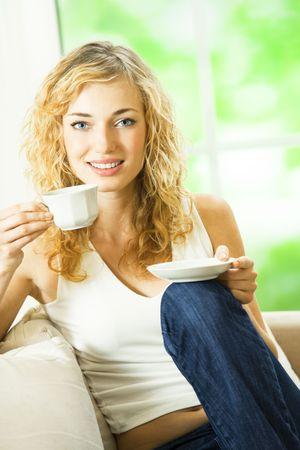 donna che beve il caff�: Bere caff�, a casa di giovane donna sorridente felice