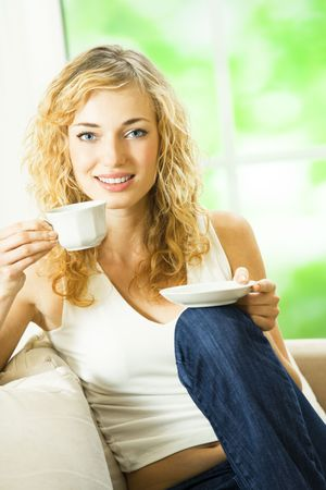 Young happy smiling woman drinking coffee, at home photo