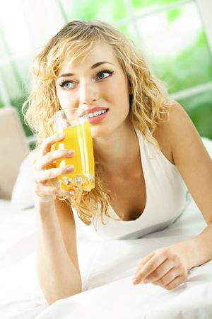 Happy young woman with juice of tropical fruit on bed photo