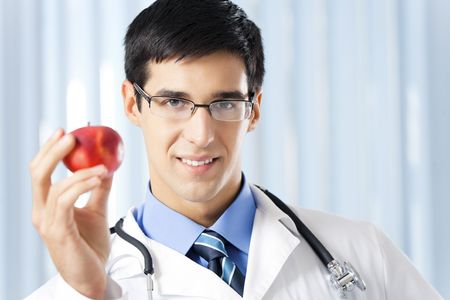 Happy smiling doctor with apple, at office photo