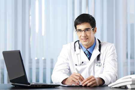 medical practice: Successful doctor with laptop, at office