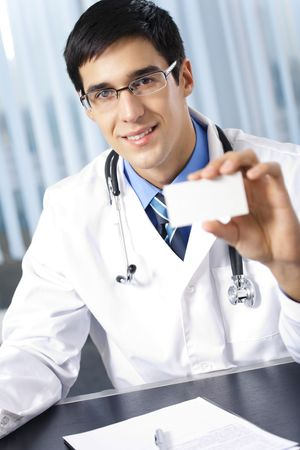 Happy doctor giving business card, at office photo