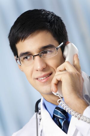 Successful doctor with phone, at workplace photo