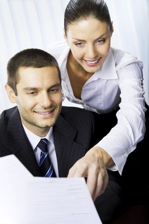 Two businesspeople, or businesswoman and client, with document at office Stock Photo - 7717625