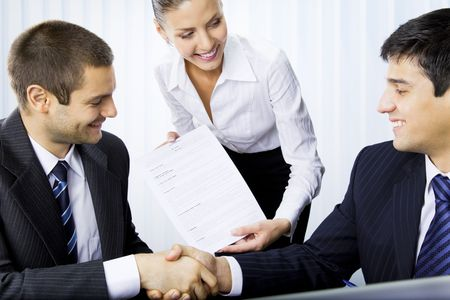 handshaking: Three businesspeople handshaking with document at office