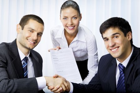 Three businesspeople handshaking with document at office  Stock Photo - 7717678