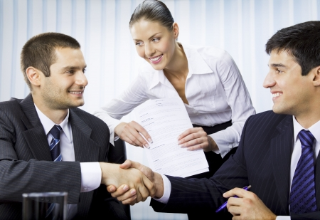 firmando: Tres empresarios handshaking con documento en Oficina