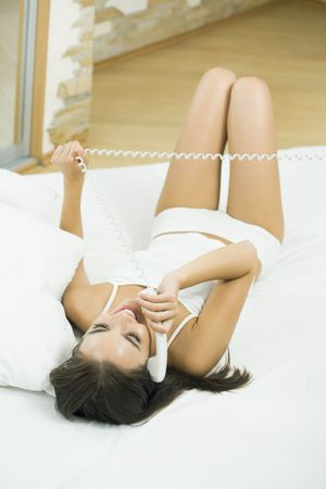 Young happy woman talking on phone at bedroom Stock Photo - 7778429