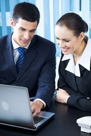 Two businesspeople working with laptop at office photo