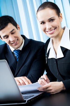 Two happy businesspeople working together at office photo