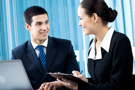 Two happy businesspeople working together at office. Focus on woman. Stock Photo - 7875247