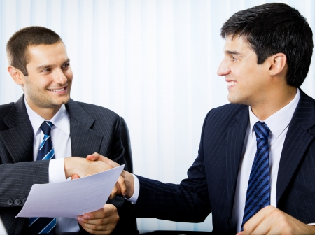 işadamları: Two businesspeople, or businessman and client, with document handshaking at office