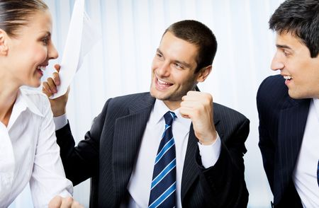 successfull: Happy successful gesturing businesspeople with document at office Stock Photo