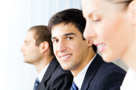 Three young successful businesspeople at office, with selective focus on man photo