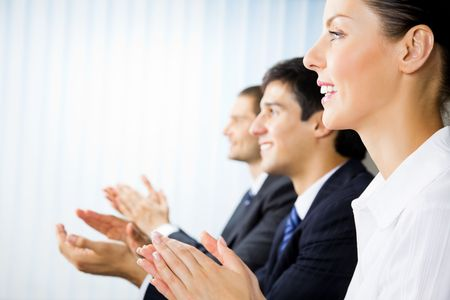 workgroup: Three happy clapping businesspeople at presentation, meeting, seminar or conference Stock Photo