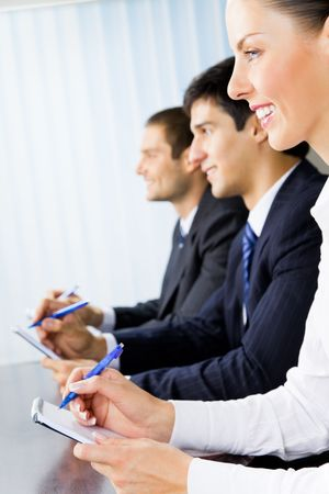 Three young successful businesspeople at meeting, presentation or conference photo