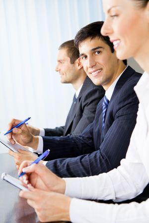 Three young successful businesspeople at meeting, presentation or conference. Selective focus on one of men. photo