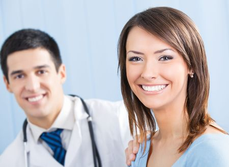 doctor visit: Happy female patient and doctor at office. Focus on woman.