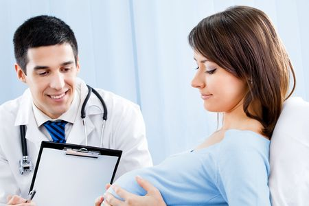 Doctor and pregnant woman with prescription at office photo