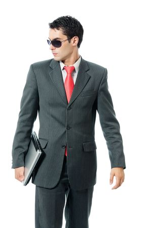 Businessman or hacker in sun glasses with laptop, isolated on white background photo