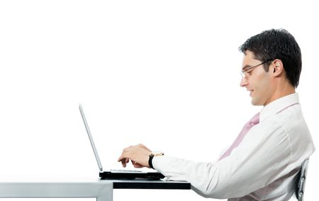 Successful happy smiling businessman working with laptop at workplace, isolated on white background photo