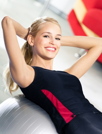 gym ball: Portrait of young happy smiling woman in sportswear, doing fitness exercise with fit ball, indoors