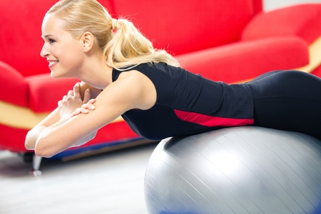 Portrait of young happy smiling woman in sportswear, doing fitness exercise with fit ball, indoors Stock Photo - 8266025