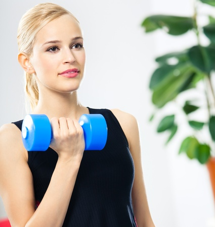Portrait of young happy smiling woman in sportswear, doing fitness exercise with dumbbell, indoors photo