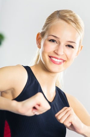 Portrait of young woman in sportswear, doing fitness exercise, indoors photo