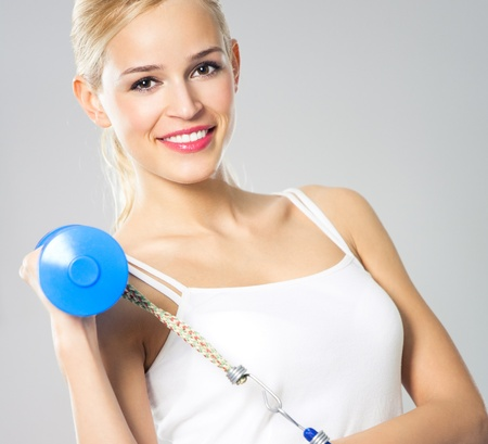 Portrait of young woman in sportswear, doing fitness exercise with dumbbell and expander photo