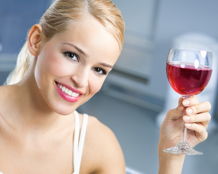 Portrait of young woman with glass of red wine, indoors photo