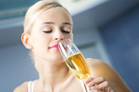Young woman with glass of champagne, indoors photo
