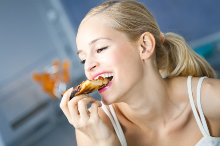 or hungry: Young happy woman eating pizza, indoors