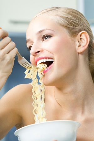 Happy woman eating spaghetti indoors Stock Photo - 8266020