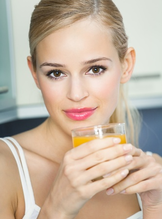 Portrait of young woman with orange juice, indoors Stock Photo - 8266005