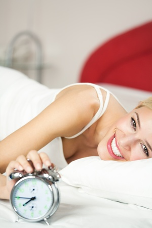 Young happy smiling woman with alarmclock on the bed at the morning photo