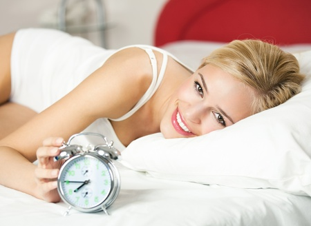 Young happy smiling woman with alarmclock on the bed at the morning Stock Photo - 8265976
