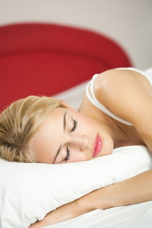 sleeping girl: Young attractive blond woman sleeping on bed Stock Photo