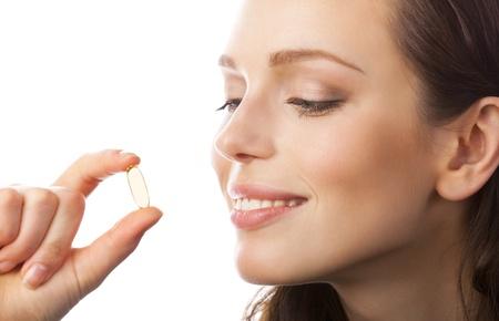 pills in hand: Retrato de mujer con c�psula de aceite de pescado de Omega 3, aislado en fondo blanco Foto de archivo